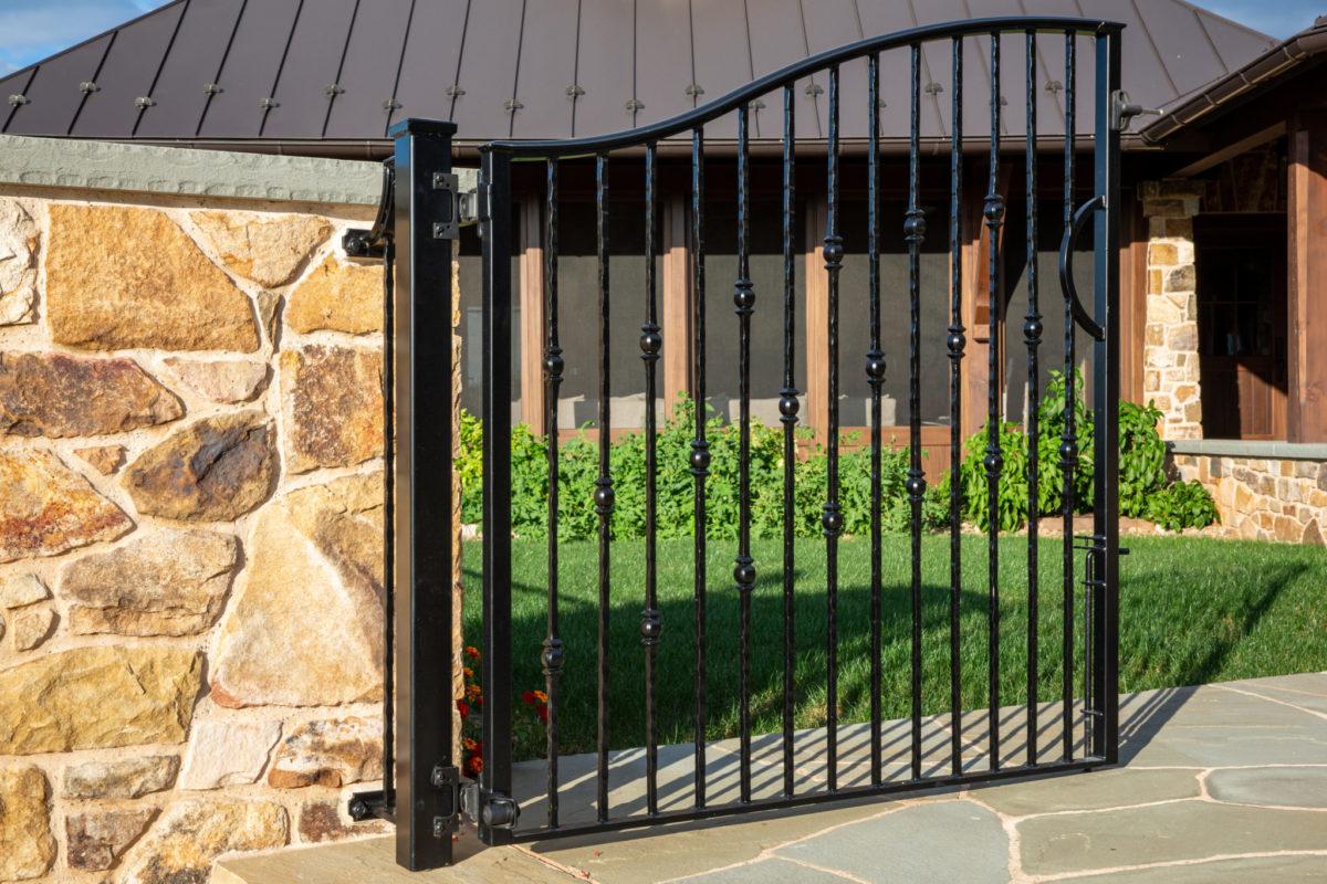 custom made black steel gate sitting in front of metal seam room